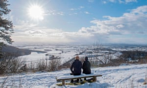 A couple sit on a bench overlooking the fields of Thirsk at Sutton bank National Park Centre in North Yorkshire