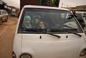 Displaced Syrians transport their belongings through the town of Hazano as they flee northwards during an ongoing regime offensive.