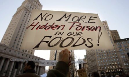 "A protester holds a sign reading ""No More Hidden Poison in Our Foods"" at a rally against trans fats in 2006 in New York City"