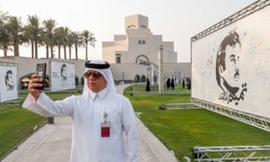 A visitor takes a selfie during an exhibition of artworks Doha Qatar