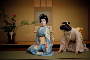 Mayu adjusts Koiku's kimono, both of who are geisha, as Koiku wears a protective face mask to pose for a photograph, before working at a party being hosted by customers, where they will entertain with other geisha, at Asada, a luxury Japanese restaurant