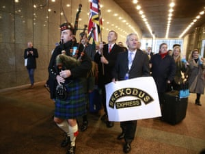 A piper leads British MEPs out of the European parliament with their luggage to take their train back to Britain