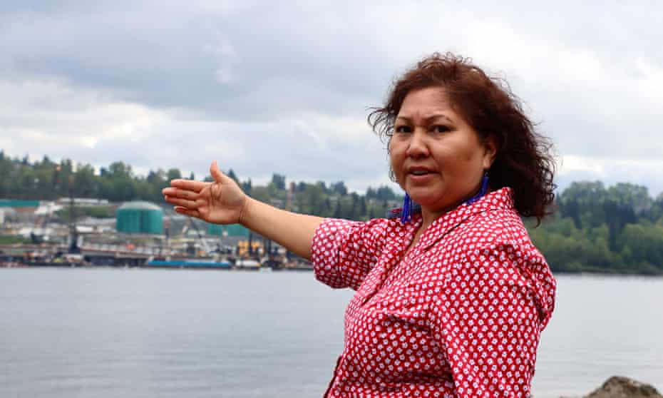 Charlene Aleck. Behind her is Trans Mountain's marine terminal near Vancouver that will grow significantly as part of the project. She is standing on the Tsleil-Waututh Nation's reserve.