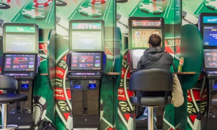 Woman using one of a line of fixed-odds betting terminals