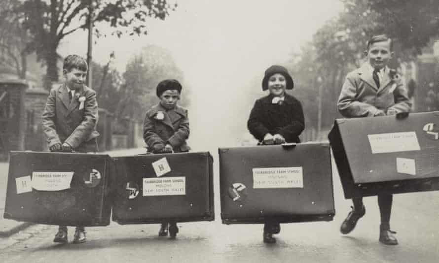 Four children carrying large suitcases