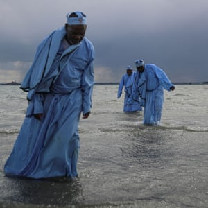 Senior members leave the sea after leading the mass baptism