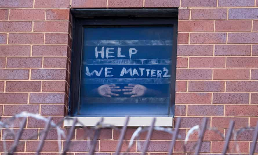 Signs pleading for help are seen in the windows at the Cook county jail complex in Chicago, Illinois, on 9 April.