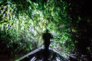 Jose Miguel Santi leads a night hunting expedition on his cousin's boat in the Ecuadorean Amazon.