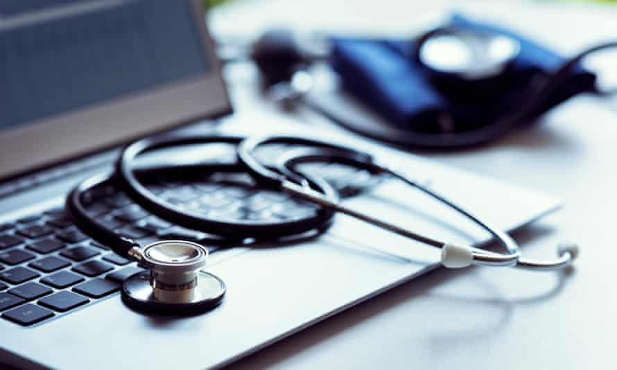 Stethoscope on laptop keyboard in doctor surgery with blood pressure monitor
