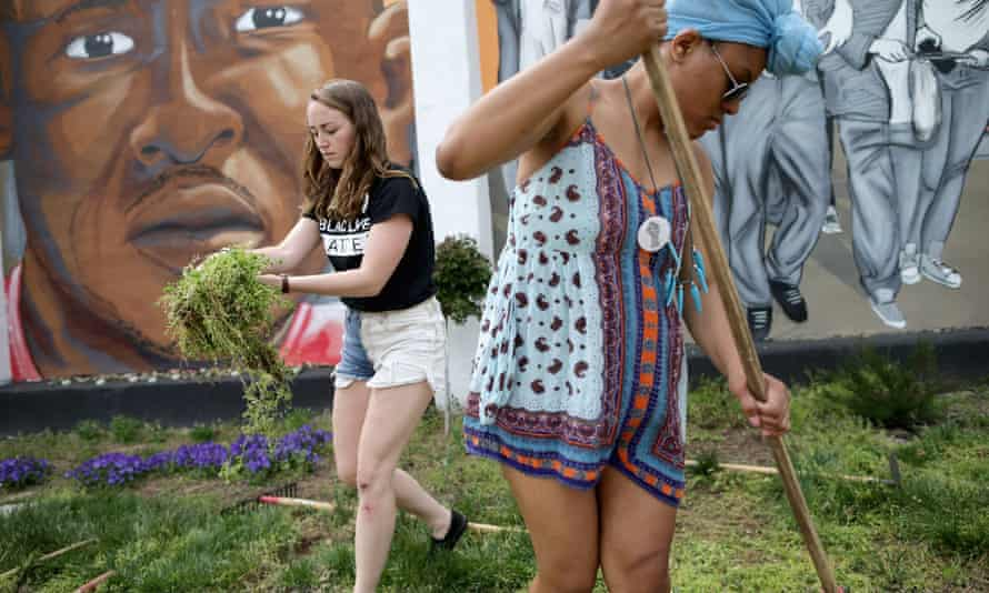 Loyola University students Kate Spence, 21, and Kassina Dwyer, 18, work to clear and landscape the garden in front of a large memorial mural of Freddie Gray on Tuesday in Baltimore, Maryland.