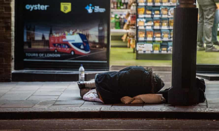 A homeless person sleeps on a London street.