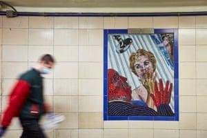 Leytonstone psychodrama. Masked man passes mural of Alfred Hitchcock's Psycho shower