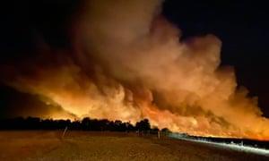 a huge plume of orange smoke billows into the sky