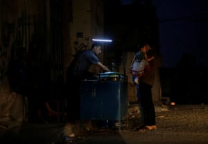 A man sells falafel as he uses a battery-powered light during power cut