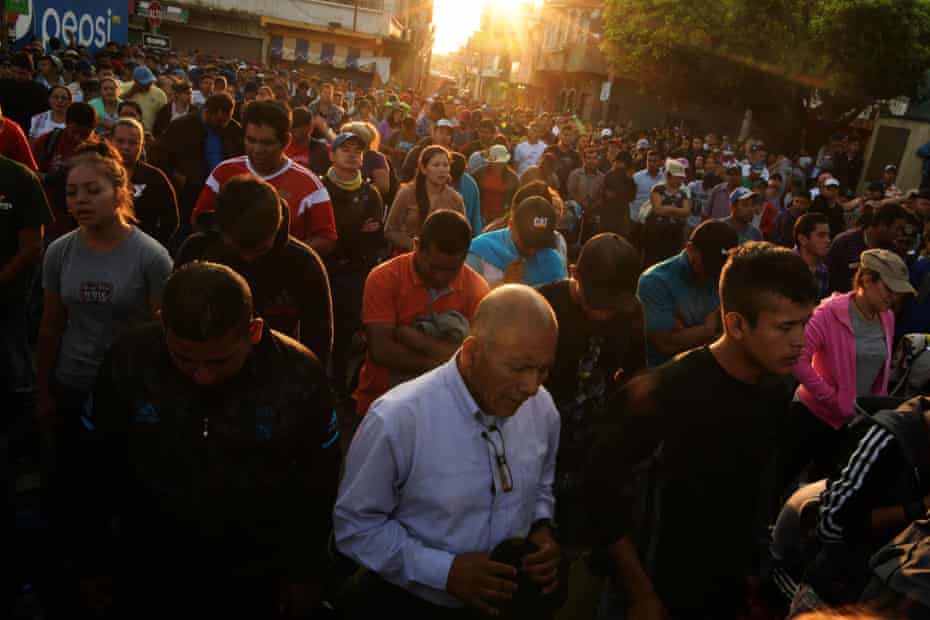 Salvadorean migrants pray as they wait to enter the Guatemala-Mexico international border bridge in Ciudad Tecun Uman, Guatemala.
