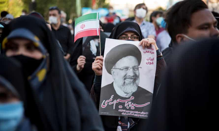 Supporters hold a poster of the hardline candidate Ebrahim Raisi in Tehran on 11 June.