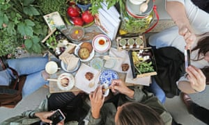 Photo taken from above of customers eating at tables outside La Guinguette d'Angele, Paris.