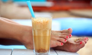 A glass of iced coffee with a straw placed on wooden planks. Women's sandy feet in the background