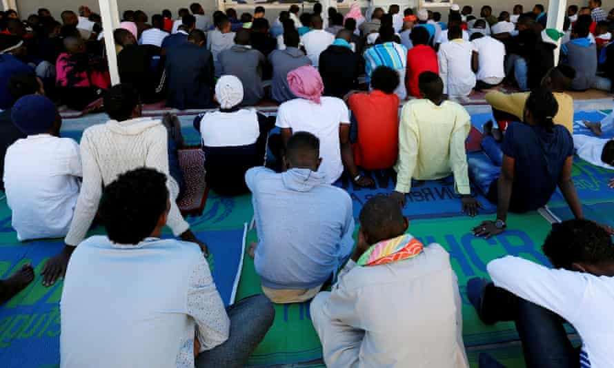 Refugees pray in a detention centre in Tripoli