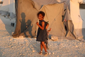Two Syrian girls stand next to a tent at a camp for displaced people in the country's northern Idlib province