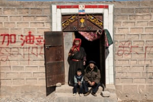 A Tibetan family in the village of Suojia, which lies at the heart of the natural park. A ceramic portrait of Chairman Mao hangs above the door.