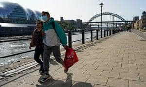 A couple walking along Newcastle quayside.