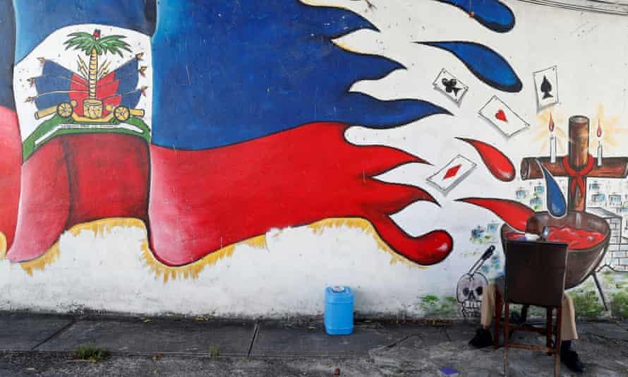 Un hombre se sienta junto a un mural en el barrio Little Haiti de Miami.