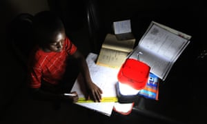 A student does his homework using a solar lantern in Zimbabwe