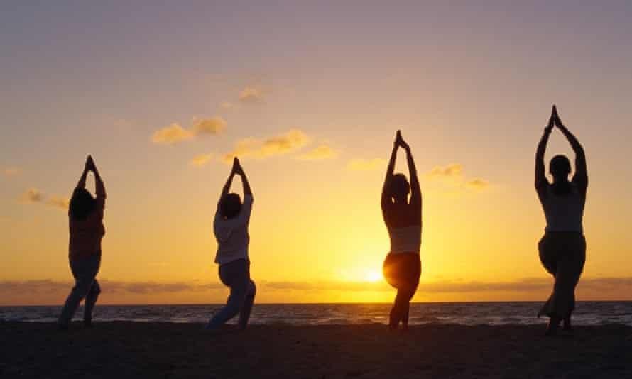 Four people doing yoga on a beach.