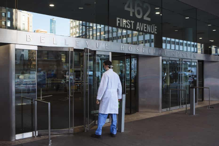 A medical worker wearing a protective mask enters Bellevue Hospital in New York.