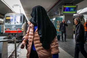 A passenger covers his face as people get off the train arriving  in Naples, southern Italy, from Milan