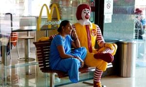Indian woman sitting on bench at McDonald's fast food restaurant, Varanasi, Uttar Pradesh, India, Asia C3TKG0 Indian woman sitting on bench at McDonald's fast food restaurant, Varanasi, Uttar Pradesh, India, Asia