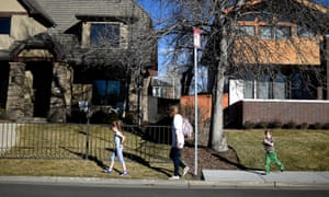 A family walks between sections of sidewalk and non-sidewalk in Denver