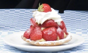 A pastry base with layers of strawberries and cream built into a pyramid