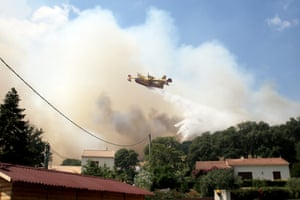 A plane drops water over a forest fire near the village of Ortale in Corsica