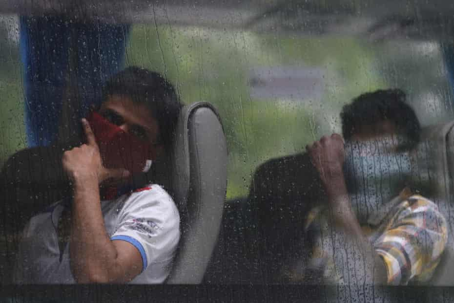 Foreign workers wait to be transferred from their dormitory in Singapore after an outbreak among migrant workers.
