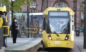 """Commuters wait to board a tram in Manchester, after the Prime Minister Boris Johnson said people who cannot work from home should be """"actively encouraged"""" to return to their jobs"""