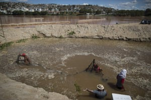Fishermen use a net in a temporary pool they built to protect fish and other aquatic life in the Doce River from polluted waters, in Colatina, Brazil. The Samarco mine dam disaster contaminated the river, devastating wildlife and fish