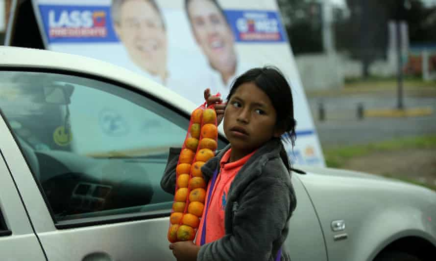 A child sells fruits near an election poster for opposition candidate Guillermo Lasso.