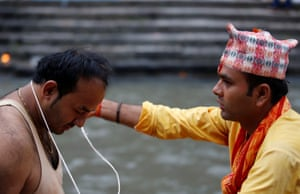 A devotee is given a new sacred thread. The thread, known as a Janai is a cord made of cotton threads worn diagonally on the torso