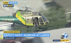 Image taken from video provided by KABC-TV on 21 August shows a sheriff's department helicopter with a sniper searching for a gunman at large in Lancaster, California.
