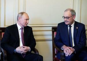 Russian President Vladimir Putin (L) talks with Swiss President Guy Parmelin (R).