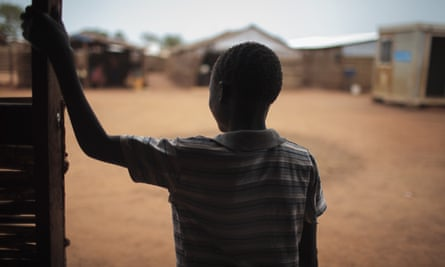 Thirteen-year-old Batista was drugged and raped in the middle of the night. He stands in the doorway of a psychosocial support clinic in a camp for the internally-displaced in Wau, South Sudan.