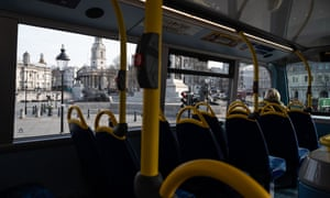 A lone commuter sits onboard a bus as it passes a near-empty Trafalgar Square in London