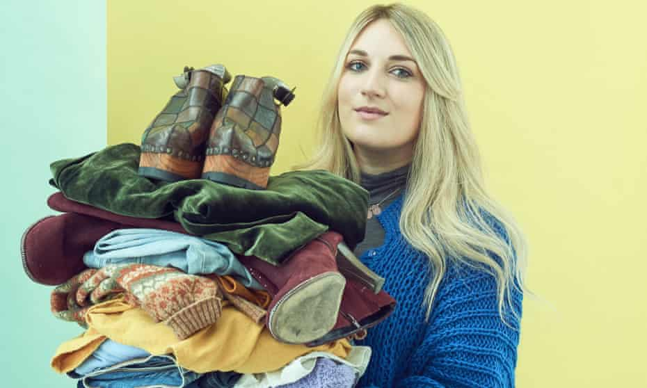 Lauren Bravo holding a pile of worn clothes.