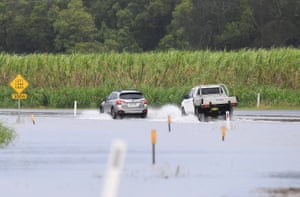 Cars drive through a flooded road at Tumbulgum, NSW.