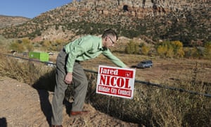 Jared Nicol plants his campaign sign for city council in Hildale, Utah.
