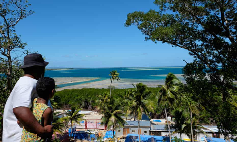 Jona Ratu and his daughter look at the channel dug into the reef on Malolo Island by Chinese company Freesoul.