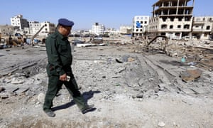 A Yemeni police officer inspects the site of an alleged Saudi-led airstrike, damaging nearby schools.