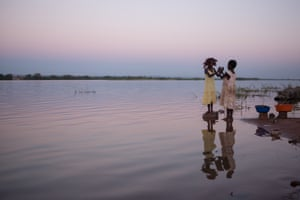 Two girls play together during sunset on the banks of the Luapula river